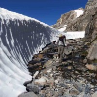 Heavy snow clings to the Sierra on the south side of Muir Pass in Kings Canyon National Park in mid-August, but doesn't deter this hiker. Photo by Jim Backhus