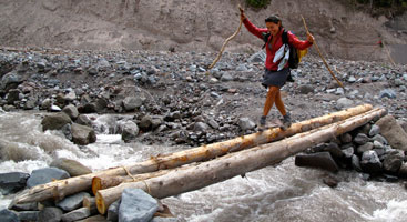 Hiker crossing a log on the Pacific Crest Trail. Photo by Stephanie White