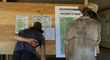 Thruhikers reading information about a fire closure that forced them to skip around.