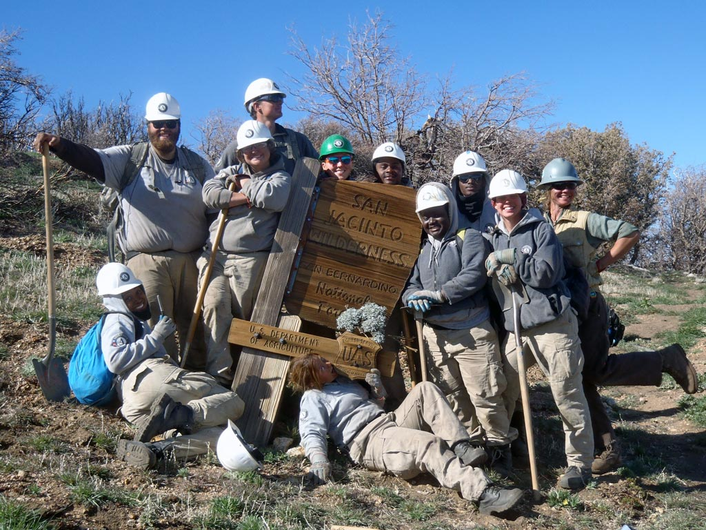 The entire crew posing, smiling (and chewing on the sign) at the San Jacinto Wilderness sign. Heidi Brill is on the far right.