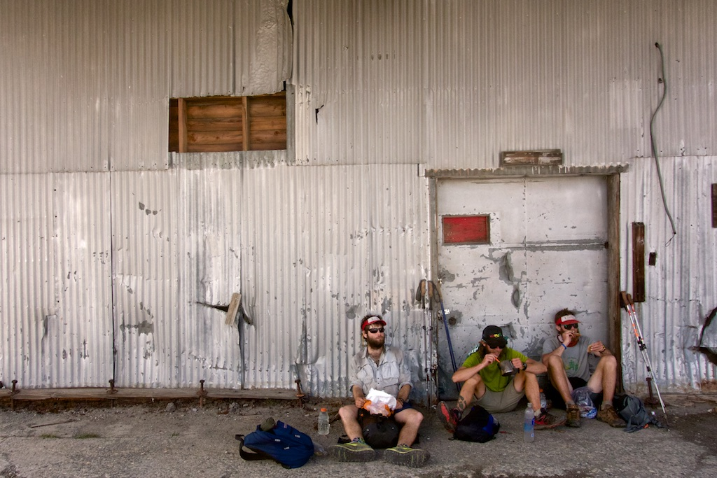Thru-hikers rest for lunch in the shade of a utility building near Truckee. High Sierra, California