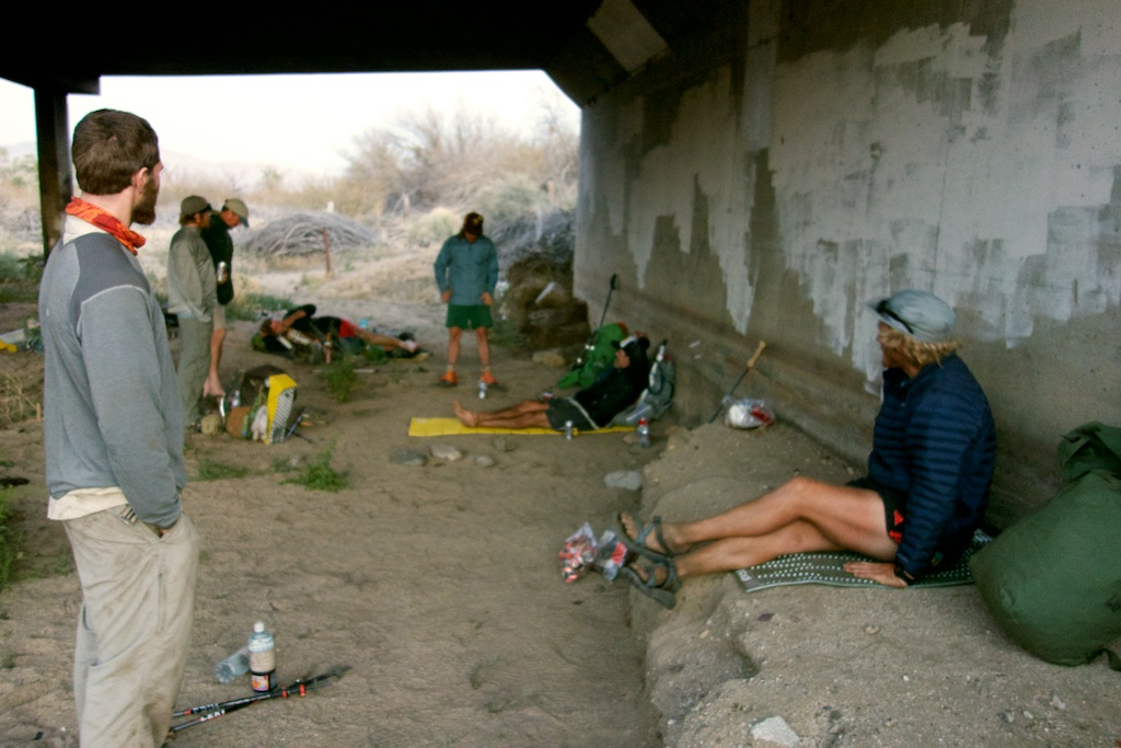 Thru-hikers wait out the mid day sun under a bridge in Scissors crossing. Southern California
