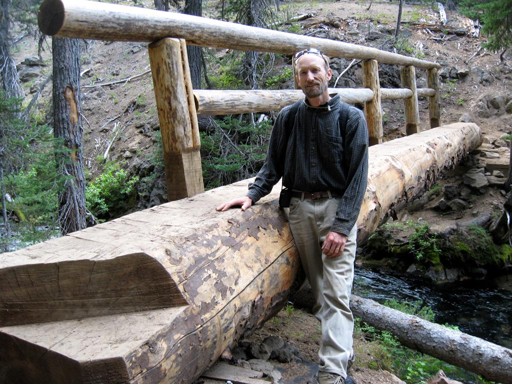 John Schubert with one of his traditional joinery bridges along the North Fork Trail.  Photo by Ellen Santasiero