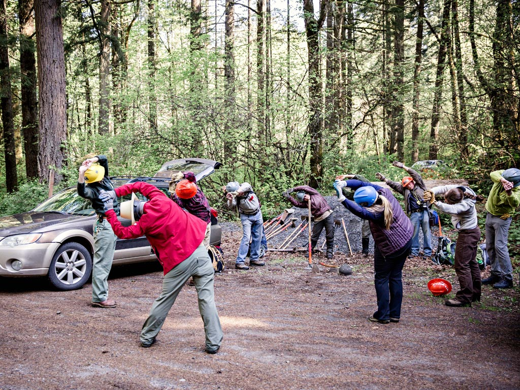 Limbering and stretching, part of the trailhead ritual before volunteering on the PCT. Photo: Gray Feather Photography.