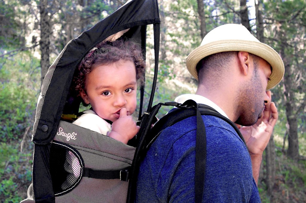 A shade on a baby carrier is a very good idea when it's sunny or wet. FLICKR/IanDKeating