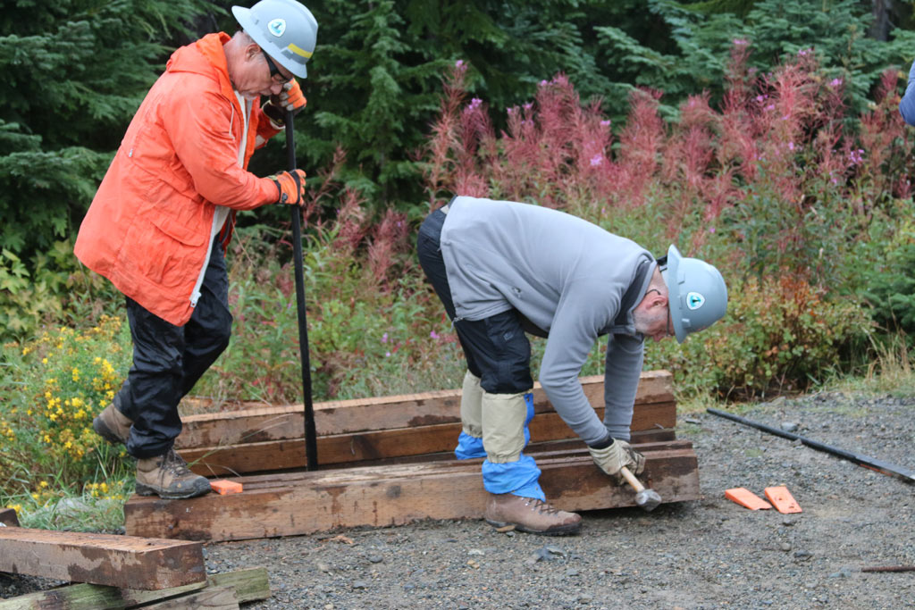 Volunteers Jack Jensen and Paul Gardiner work to separate timbers that will be used to construct new turnpikes.