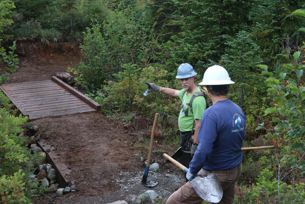 Crew Leader Barry Teschlog and PCTA Regional Representative Bill Hawley inspect safety improvements to a creek crossing.