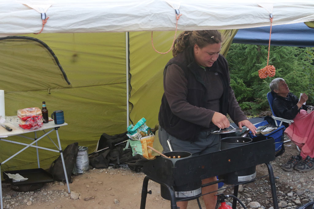 Volunteer cook Sonya Rodgers begins the evening meal under cover.