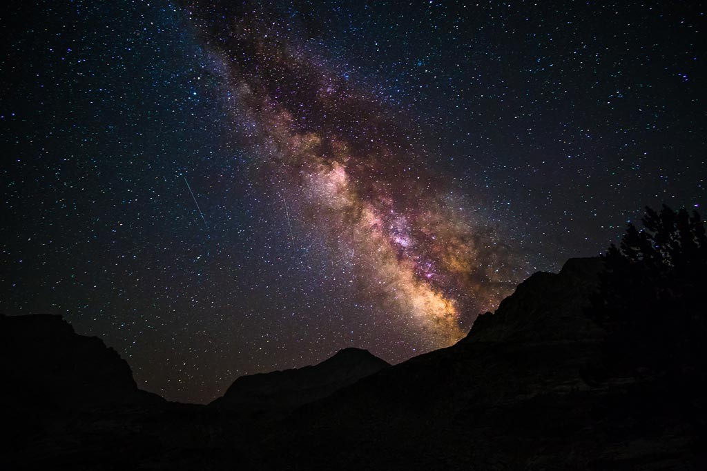 The milky way shines bright above the dark Sierra.