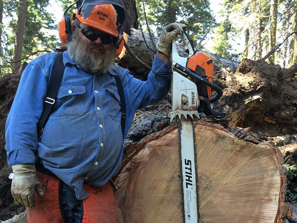 """Charles """"Pounder"""" Williams with one of the many, many trees that he's cleared off of the PCT."""