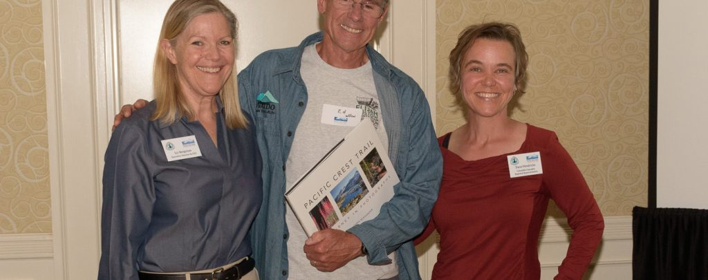 Liz Bergeron, left, and Regional Representative Dana Hendricks, right, congratulate Ed Wilson on being named Trail Maintainer of the Year for the Columbia Cascades region. Photo by Frank Gorshe.