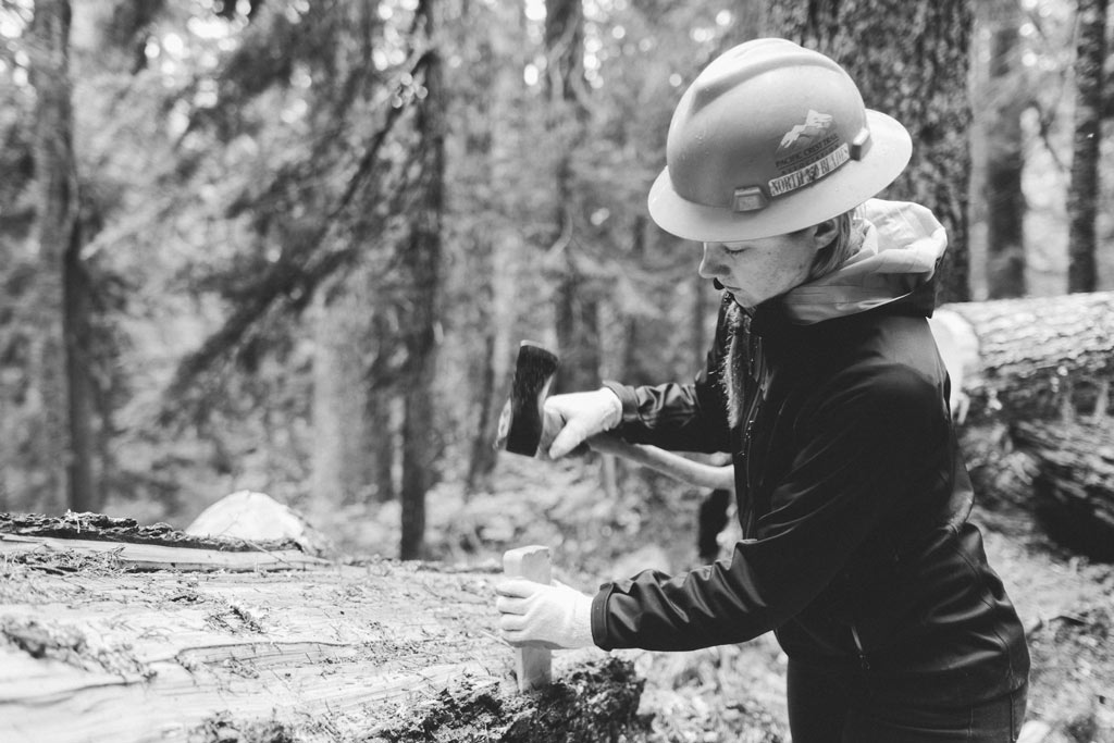 Sporting a PCTA North 350 Blades hardhat while removing bark from a tree. Photo by Vincent Carabeo/Uphill Designs.
