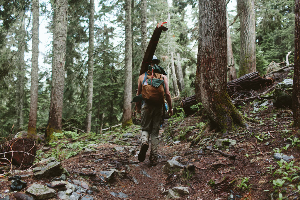 A volunteer heads to work with a crosscut saw in Washington state. Join PCTA on a volunteer trail crew. Photo by Vincent Carabeo/Uphill Designs.