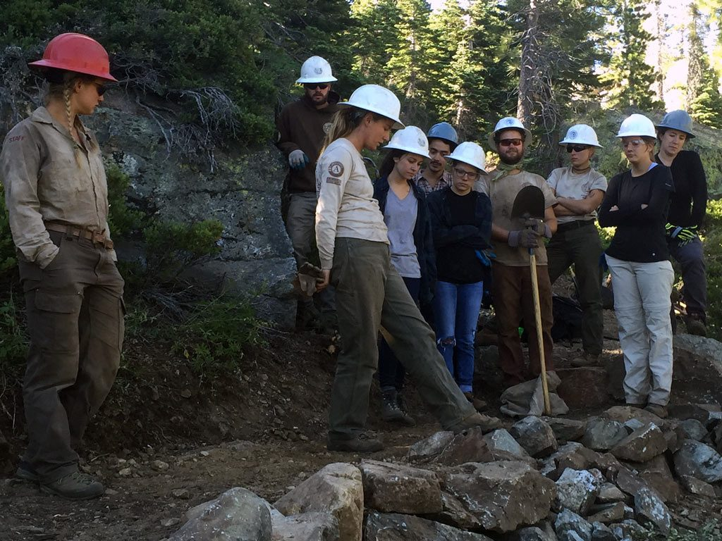Learning how to build a rock wall on a trail. ACE corp crew members teach PCTA volunteers about dry masonry