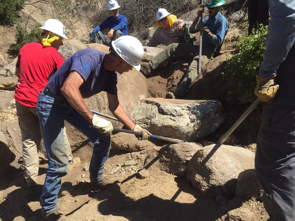 Volunteers are taught to handle and use rock bars while constructing rock-retaining walls – by Connor Swift