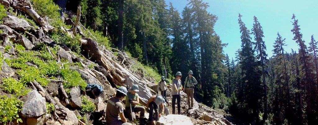 The Shale Lake volunteer trail crew discuss their plan of attack to remove a giant boulder in the middle of the trail on a steep talus slope. Pictured from front to back: Andy Milgliazzo, Jennica Tamler, Kat Wallace, Sam Hartman, Erin Mullen, Thierry Chatard. Photo by Michael Weiss