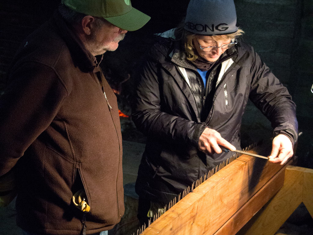 After class, volunteer saw instructor David Roe teaches volunteers how sharpen a traditional crosscut saw – by Joe Smith