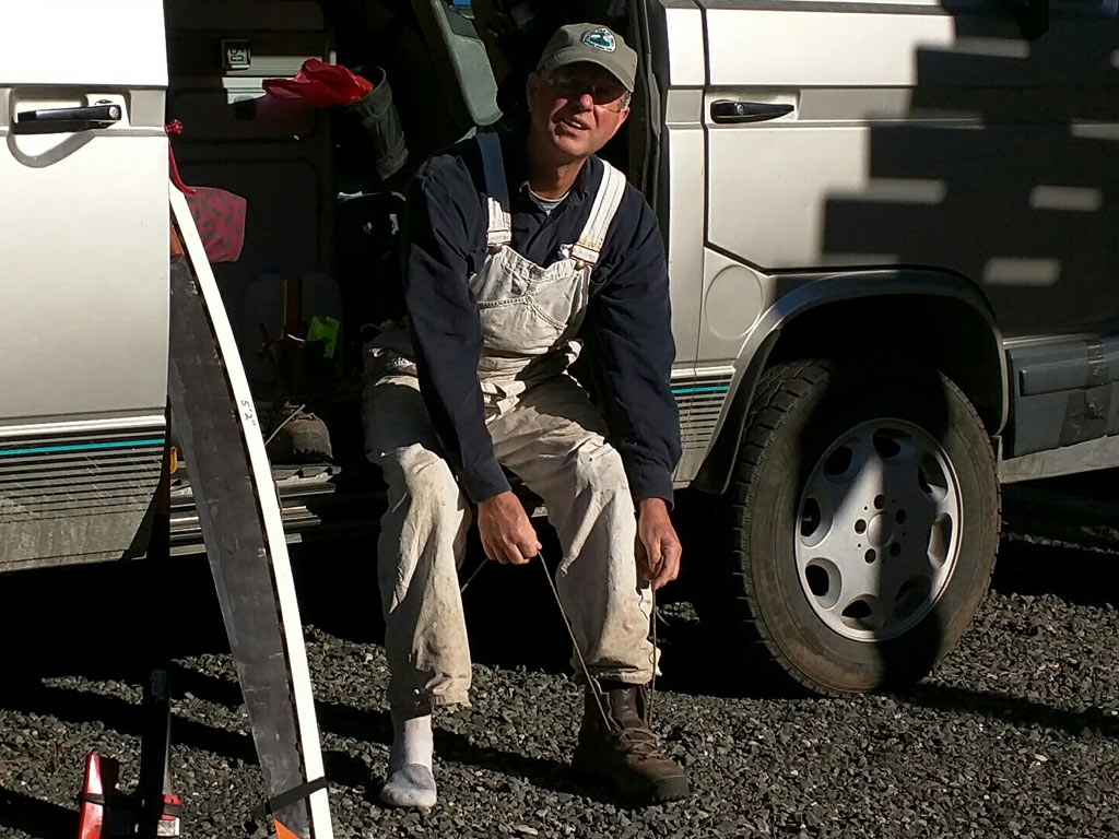 Supremely dedicated volunteer, Kim Owen, ties his newly donated Vasque boots before a day on the trail.