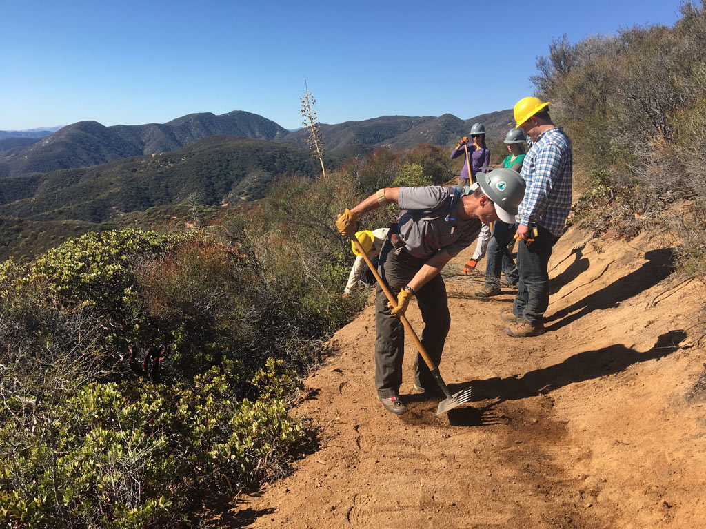 Volunteers perform final touches after the trail machine cuts through the hillside. Photo by Niki Forgues