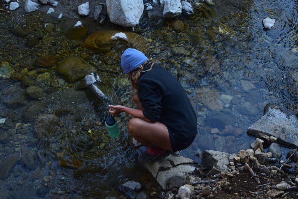 Collecting water from the wilderness. Please protect water quality by not washing your dishes, or yourself, in water sources.