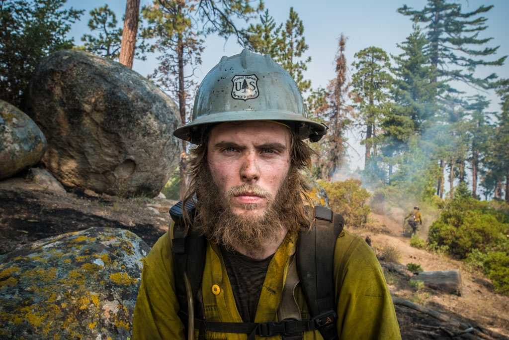 Forest Service Smith River Hotshots Forestry Technician, Shane Blair is part of an army of wildland fire fighters on the front line of our nation's response. Here is works to clear hazard trees during a fire on Sequoia National Forest, August 23, 2016. USDA Photo by Lance Cheung.