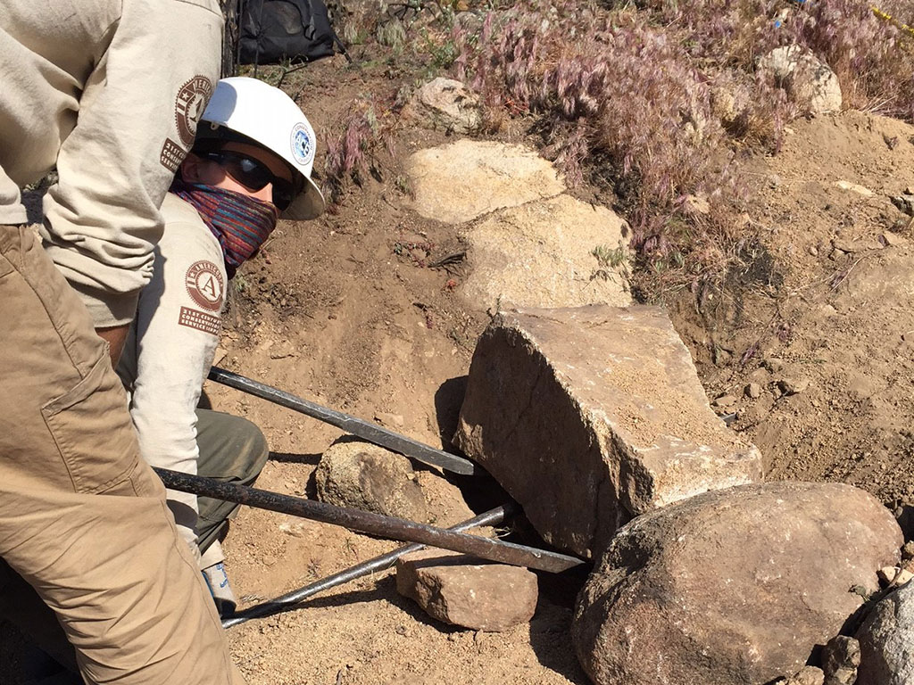 NCCC trail crew uses a rock bar to move a rock
