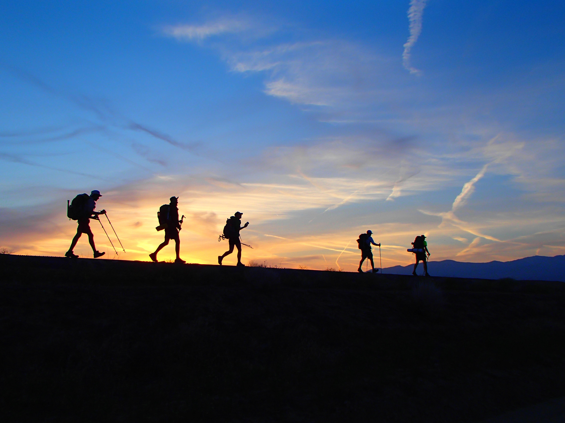 Sunset behind hikers walking along the top of the Los Angeles Aqueduct in the Mojave Desert. Photo by Clayton Feider-Sullivan.