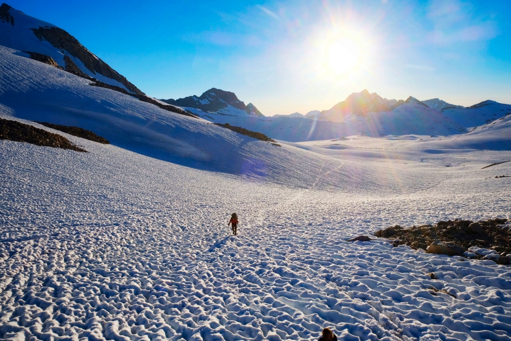 Hiking across an endless field of sun-cupped snow in the Sierra Nevada