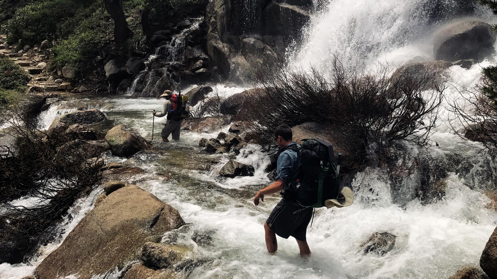 Two hikers attempt a safe crossing of a river while backpacking.