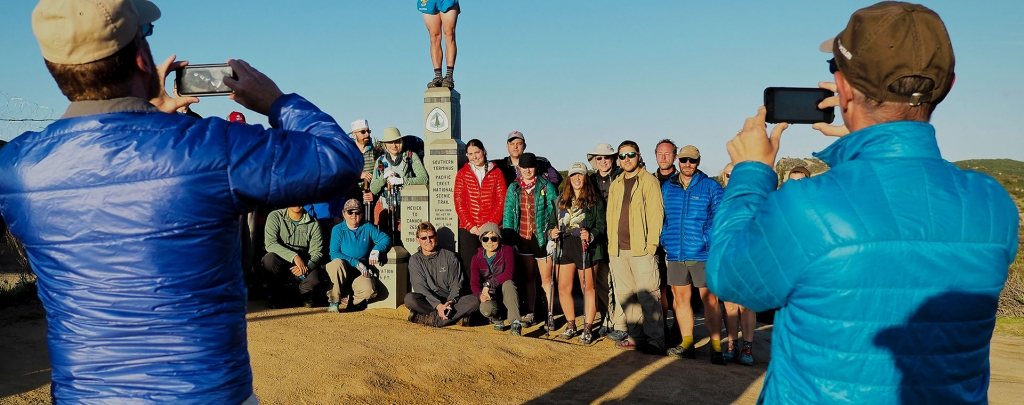 "Pacific Crest Trail hikers pose for photos at the Southern Terminus near Campo, CA. Photo by Lon ""Halfmile"" Cooper"