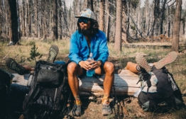 """Shermin """"Happy Feet"""" Maningas rests on a log while two trail family members, Indigo and LL Cool Juniper, lay on the ground resting their feet. Photo by Shermin Maningas."""